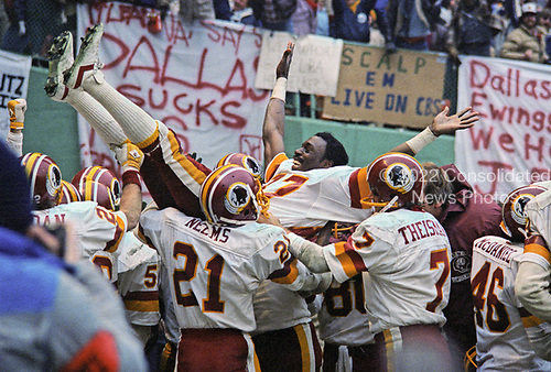 Washington Redskins wide receiver Charlie Brown (87) is carried by his teammates as they celebrate the 10 yard interception return for a touchdown by defensive tackle Darryl Grant (77) in the fourth quarter of the National Football Conference (NFC) Championship Game against the Dallas Cowboys at RFK Stadium in Washington, D.C. on Saturday, January 22, 1983.  Recognizable with brown are kick return specialist Mike Nelms (21) and quarterback Joe Theismann (7).  The Redskins won the game and the championship 31 - 17.<br /> Credit: Arnie Sachs / CNP