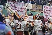 Washington Redskins wide receiver Charlie Brown (87) is carried by his teammates as they celebrate the 10 yard interception return for a touchdown by defensive tackle Darryl Grant (77) in the fourth quarter of the National Football Conference (NFC) Championship Game against the Dallas Cowboys at RFK Stadium in Washington, D.C. on Saturday, January 22, 1983.  Recognizable with brown are kick return specialist Mike Nelms (21) and quarterback Joe Theismann (7).  The Redskins won the game and the championship 31 - 17.<br />