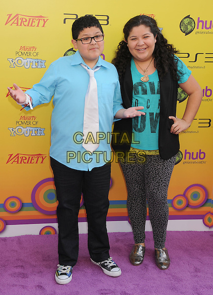 Rico Rodriguez & Raini Rodriguez.Variety's 5th Annual Power Of Youth event presented by The Hub at Paramount Studios in Hollywood, California, USA..October 22nd, 2011.full length white tie blue shirt black trousers glasses leopard print leggings grey gray sleeveless hands arms brother sister family siblings.CAP/ROT/TM.©Tony Michaels/Roth Stock/Capital Pictures
