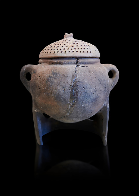 Hittite terra cotta cooking pot with perforated lid on a charcoal burner pot stand. Hittite Empire, Alaca Hoyuk, 1450 - 1200 BC. Çorum Archaeological Museum, Corum, Turkey. Against a black bacground.