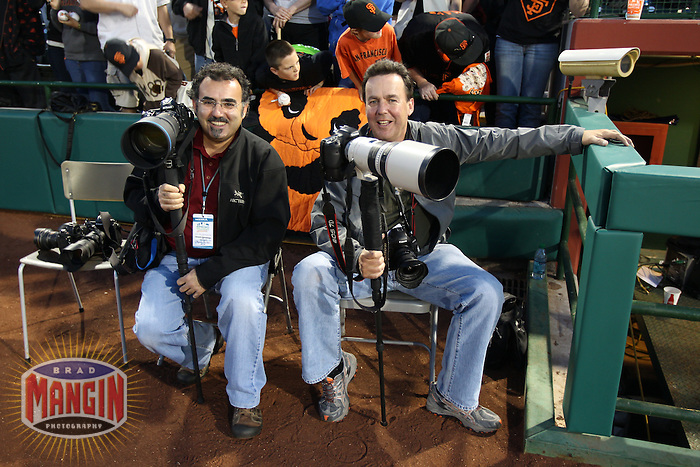 SCOTTSDALE, AZ - MARCH 08:  Photographers Kevork Djansezian and Eric Risberg take a break on the field before the spring training game between the Texas Rangers and the San Francisco Giants on March 8, 2011 at Scottsdale Stadium in Scottsdale, Arizona. Photo by Brad Mangin