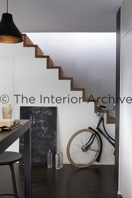 A simple open staircase ascends from the open plan kitchen area to the first floor