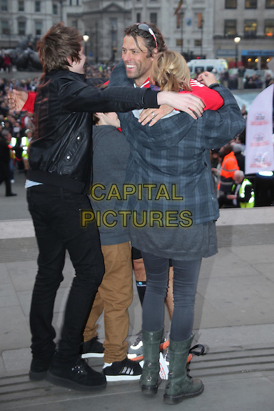 John Bishop & children .Comedian John Bishop completes triathlon in aid of charity Sport Relief, Trafalgar Square, London, England, UK, 2nd March 2012..full length red top black shorts finish sign line kids family boys hugging hugs hug .CAP/JEZ  .©Jez/Capital Pictures.