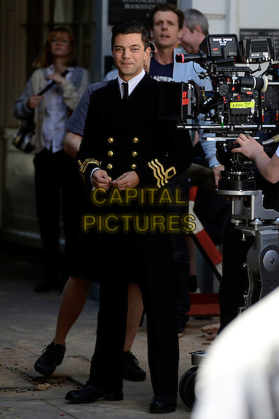 Dominic Cooper<br /> Filming on the set of 'Fleming' where Dominic Cooper stars as Ian Fleming, Central London, England.<br /> 29th June 2013<br /> tv mini series full length black suit uniform camera cast crew<br /> CAP/IA<br /> &copy;Ian Allis/Capital Pictures