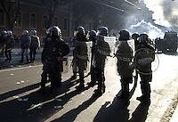 Roma,15 Ottobre 2011.Manifestazione contro la crisi e l'austerità..Corteo e scontri con le forze dell'ordine.A sinistra un agente di polizia impugna una mazza di legno