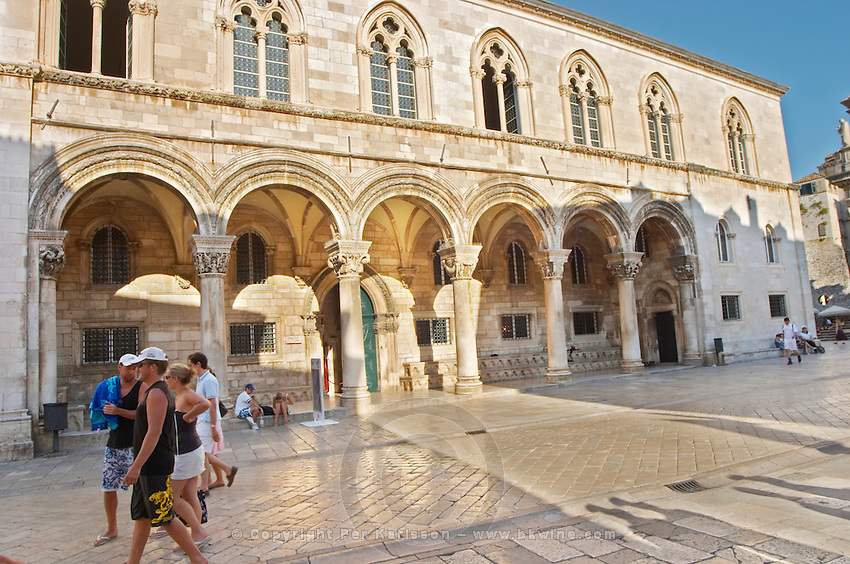 Tourists walking past in front of arched porch of the Rector's Palace Knezev Dvor on the Pred Dvorom street Dubrovnik, old city. Dalmatian Coast, Croatia, Europe.