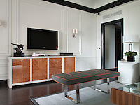 One wall of the suite living room is dominated by a large plasma screen and a wood veneer sideboard