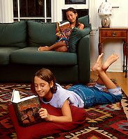 Teen and pre-teen girls read Harry Potter books in their living room. Anda and Nina Clark. Venice, California.