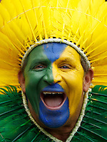 A Brazil fan wearing a feather head dress