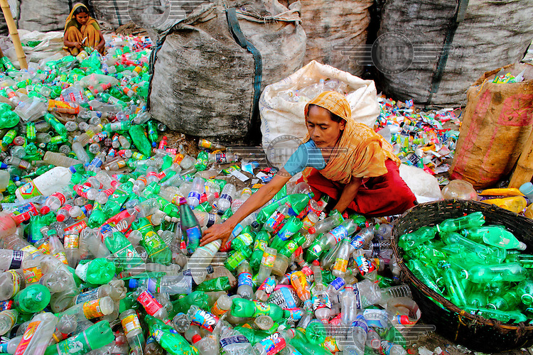 A woman, sitting among piles of plastic drinks bottles collected from Dhaka's streets, removes their labels in a factory producing PET (Polyethylene terephthalate) flakes. Bangladesh exports over 20,000 tonnes of PET flakes made in 3,000 factories located across the country in an industry worth GBP 7 million in 2010. The business is growing by 20 percent every year.