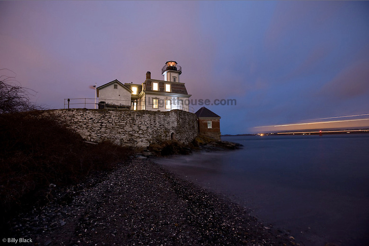 Rose Island Lighthouse glows in this long exposure night shot as a cargo ship smoothly passes by.
