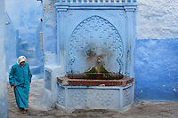 Fountain with horseshoe arch stucco decoration on a narrow street painted blue in the medina or old town of Chefchaouen in the Rif mountains of North West Morocco. Chefchaouen was founded in 1471 by Moulay Ali Ben Moussa Ben Rashid El Alami to house the muslims expelled from Andalusia. It is famous for its blue painted houses, originated by the Jewish community, and is listed by UNESCO under the Intangible Cultural Heritage of Humanity. Picture by Manuel Cohen