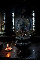 Candles and burning incense sticks and effigy in Taoist temple, the Emperor Jade Pagoda (Chua Ngoc Hoang or Phuoc Hai Tui), Ho Chi Minh City (Saigon), Vietnam
