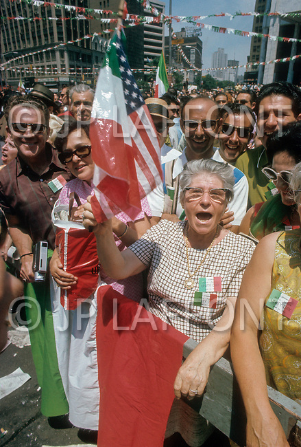 Manhattan, New York City, NY - June 29th, 1970. The Italians are a large part of the Catholic population. Here Italian-American mothers wave the US flag, but in the sky the garland have the colors of Italy.