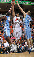Virginia Cavaliers forward Mike Scott (23) shoots between North Carolina Tar Heels forward Harrison Barnes (40) and North Carolina Tar Heels forward Tyler Zeller (44) during the game in Charlottesville, Va. North Carolina defeated Virginia 54-51.