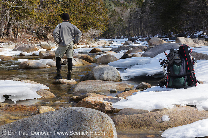 Backcountry hiker scouts out a route to cross the East Branch of the Pemigewasset River in the Pemigewasset Wilderness of Lincoln, New Hampshire USA during the winter months.