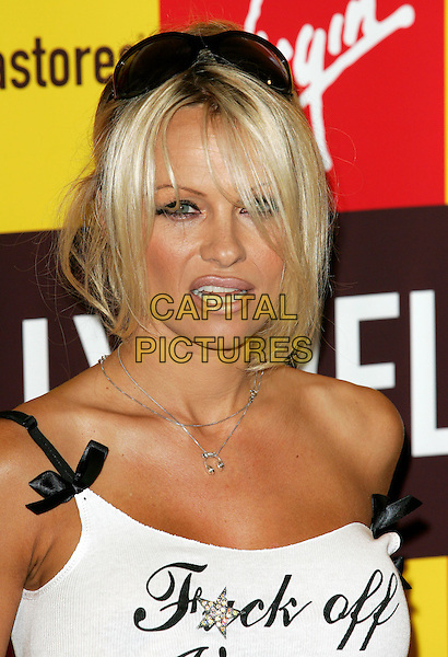 "PAMELA ANDERSON.Signs copies of her new novel ""Star"" at Piccadilly Virgin Megastore London .21 October 2004.headshot, portrait, off the shoulder, fuck off shirt, logo, slogan.www.capitalpictures.com.sales@capitalpictures.com.© Capital Pictures."