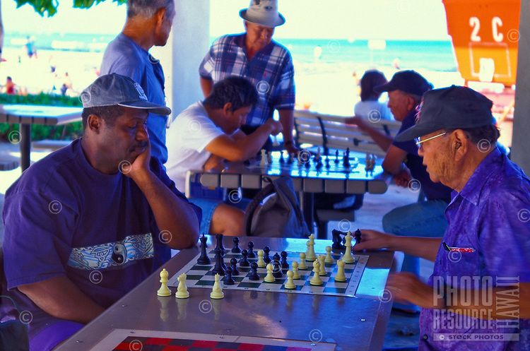 Men gather under covered shelters on Kalakaua ave. near Waikiki Beach to relax and test their skills at a gentlemens game of chess. Waikiki  Beach in the background.