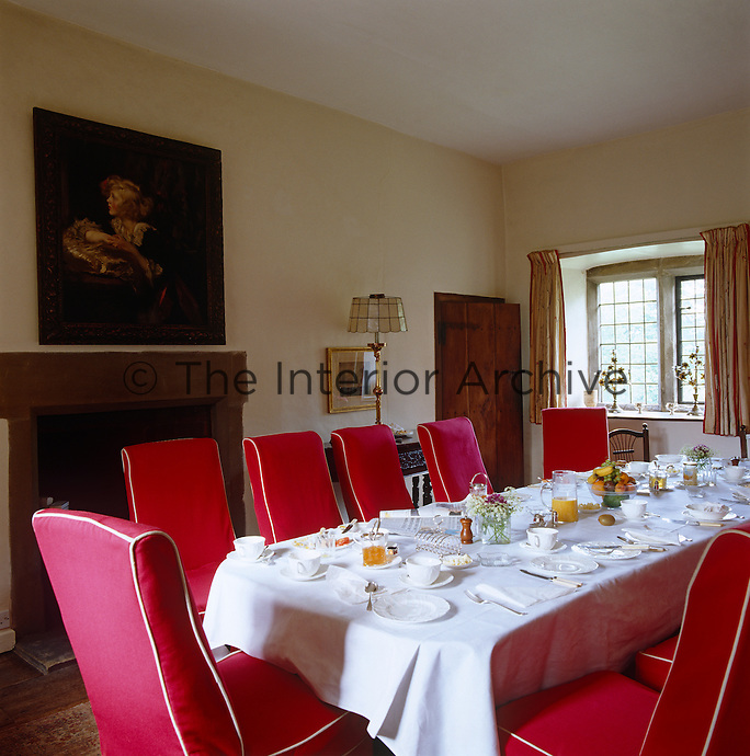 A long table in this narrow dining room is laid for breakfast with chairs upholstered in red loose covers with white piping