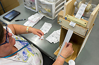 NWA Democrat-Gazette/Charlie Kaijo Cheryl Charbonneau of Rogers uses a device that allows her to put labels on packages quickly on Monday, October 9, 2017 at Open Avenues in Rogers. Open Avenues has developed a variety of devices that can accommodate people's disabilities so they can work. The organization partners with 22 different businesses and provides job and life skills training to people with disabilities, currently serving 110 clients. The clients work on projects at work stations and are paid for their work. This year they have focused on transitioning their clients into jobs in the community, many with Walmart, Zaxbys and Harp's.
