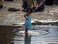 Young girl enjoys a water puddle at a Pool Parties Concert in McCarren Park , Brooklyn NYC