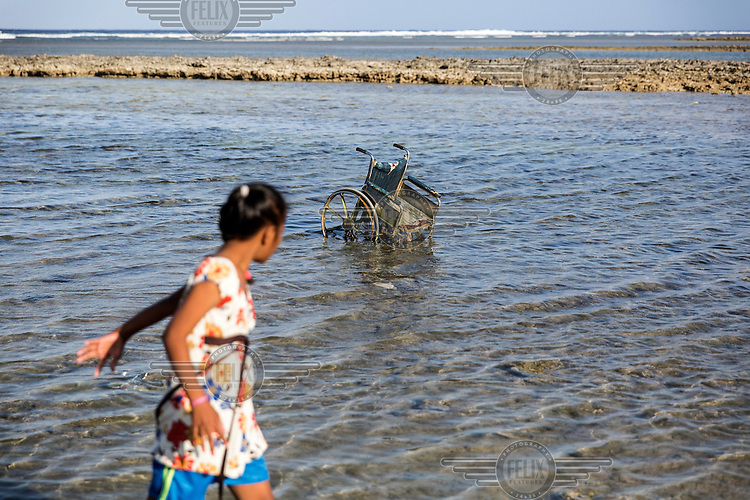 A girl passes by an abandoned wheelchair in the sea off Jenrok village.