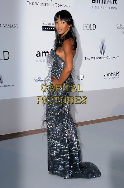 NAOMI CAMPBELL.arrivals at amfAR's Cinema Against AIDS 2010 benefit gala at the Hotel du Cap, Antibes, Cannes, France during the Cannes Film Festival.20th May 2010.amfAR full length long maxi dress silver feathers hand on hip side strapless  grey gray .CAP/CAS.©Bob Cass/Capital Pictures.