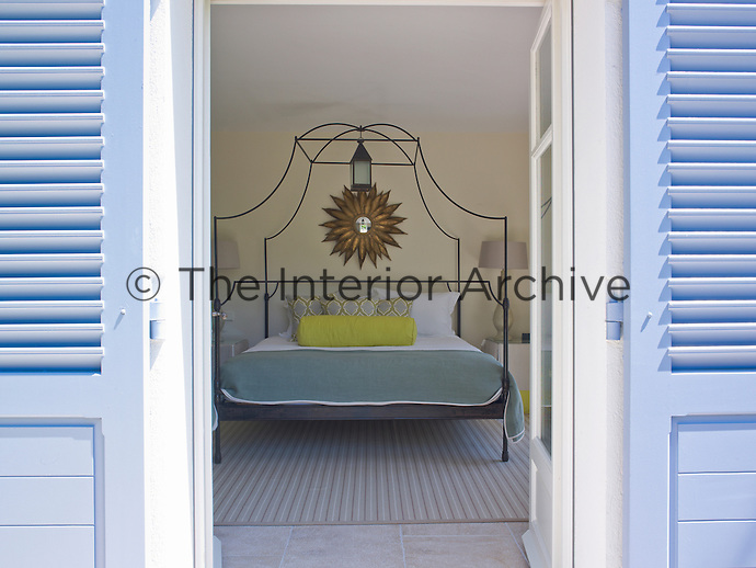 A contemporary wrought-iron bed in a guest bedroom is framed by the open blue-painted shutters