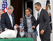 "Washington, D.C. - November 25, 2009 -- Malia Obama reaches to touch ""Courage"" the turkey pardoned by United States President Barack Obama during the traditional turkey pardoning ceremony on the North Portico of the White House on Wednesday, November 25, 2009.  From left to right: Walter Pelletier, Chairman, National Turkey Federation; Sasha Obama; ""Courage"" the Turkey; Malia Obama; and President Obama..Credit: Ron Sachs / Pool via CNP"