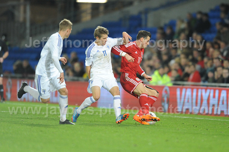 Gareth Bale of Wales beats off the challenge of Riku Riski of Finland during the Wales v Finland Vauxhall International friendly football match at the Cardiff City stadium, Cardiff, Wales. Photographer - Jeff Thomas Photography. Mob 07837 386244. All use of pictures are chargeable.