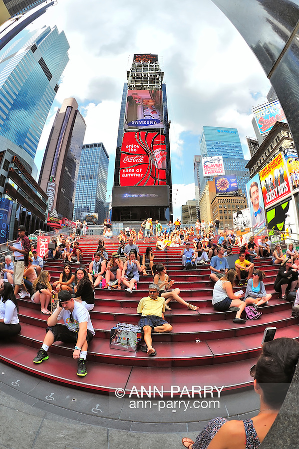 Times Square's famous red steps with tourists sitting on them, and at monument in extreme right foreground in Manhattan, New York City, NY, USA, on June 27, 2011. (180 degree fisheye lens view) NOTE: 180 degree fisheye lens view. EDITORIAL USE ONLY