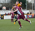 Arbroath's Mark Baxter avoids a kick in the face as he clears from Alloa's Mitchel Megginson.