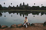 CAMBODIA  -  APRIL 7, 2005:  A woman sists on a rock in front of a pond reflecting Angkor Wat in the background at dusk in Siem Reap on April 7th, 2005 in Cambodia.  (PHOTOGRAPH BY MICHAEL NAGLE)