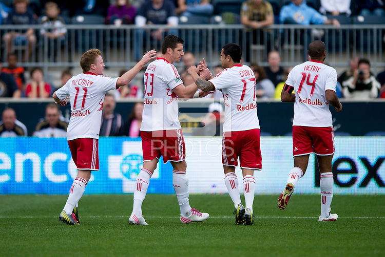 Kenny Cooper (33) of the New York Red Bulls celebrates his goal with teammates Tim Cahill (17) and Dax McCarty (11) during the game at PPL Park in Chester, PA.  New York defeated Philadelphia, 3-0.