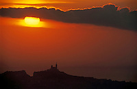 Silhouetted cityscape of Marseille at sunset, France.
