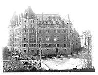 Side view of the Chateau Frontenac before the central tower was built in 1920-24, photograph, from the Archives of the Chateau Frontenac, Quebec City, Quebec, Canada. The Chateau Frontenac opened in 1893 and was designed by Bruce Price as a chateau style hotel for the Canadian Pacific Railway company or CPR. It was extended in 1924 by William Sutherland Maxwell. The building is now a hotel, the Fairmont Le Chateau Frontenac, and is listed as a National Historic Site of Canada. The Historic District of Old Quebec is listed as a UNESCO World Heritage Site. Copyright Archives Chateau Frontenac / Manuel Cohen