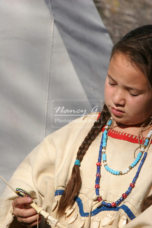 A young Native American Indian child playing with native primitive toys in South Dakota