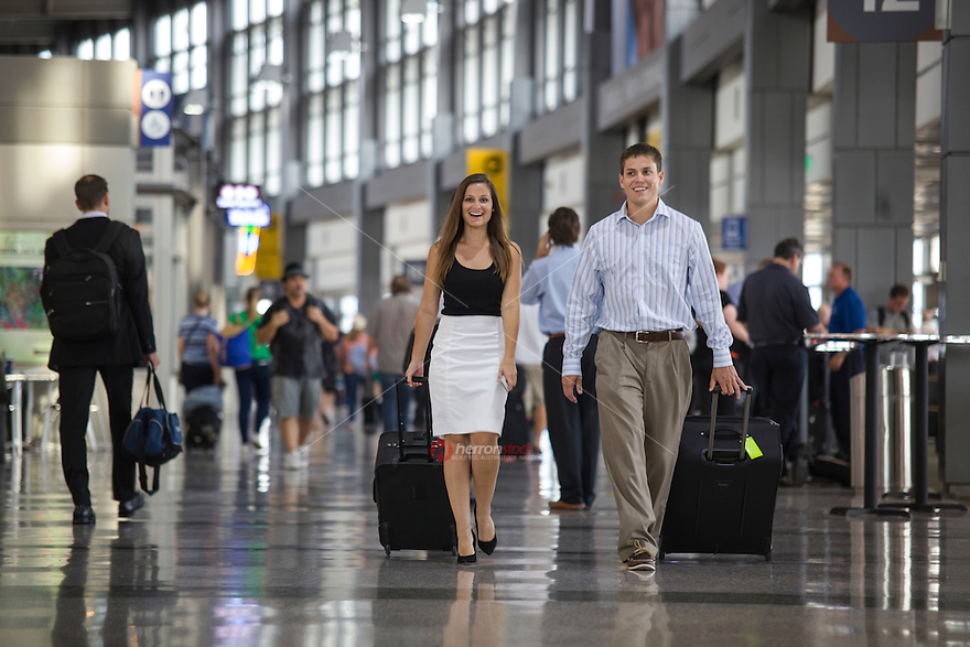View of attractive couple walking through Austin–Bergstrom International Airport (ABIA) terminal.