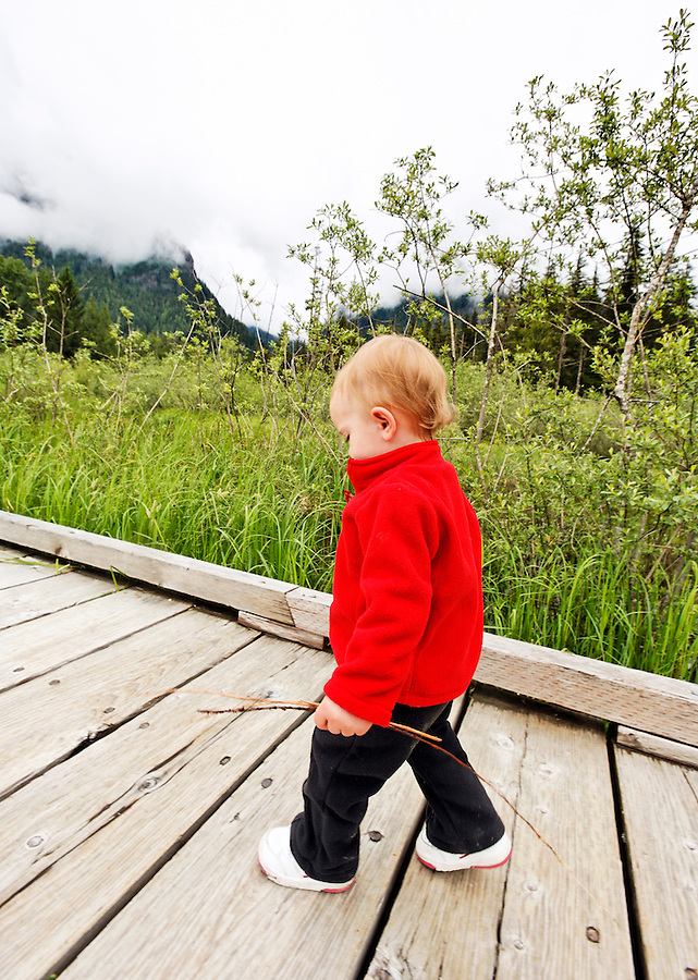 Young girl walking on wooden boardwalk trail with twigs, Big Four Ice Caves Trail, Mt Baker Snoqualmie National Forest, Washington, USA