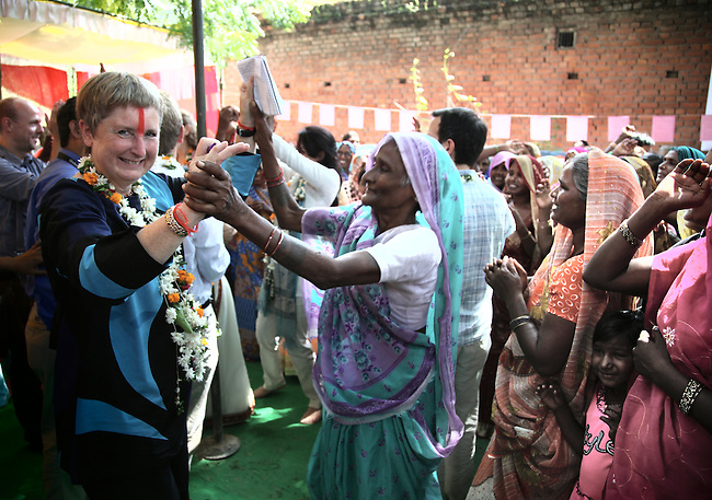 VARANASI, INDIA September 13, 2010: Marianne Barner (left) of IKEA, India dancing with  local women in Jamalpur Village in Jaunpur district outside of Varanasi, India.  IKEA Chief Executive Officer Mikael Ohlsso(far right) is in India  inspecting the social initiatives his company sponsors in collaboration with UNICEF and UNDP focusing on Womens Empowerment  through a number of programs based on self help groups (SHG).  pic Graham Crouch/UNICEF