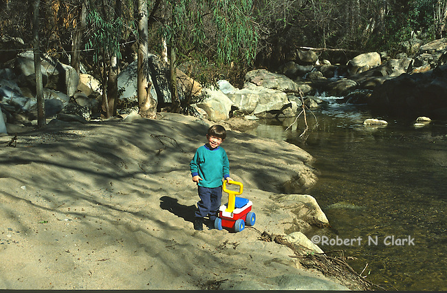 Boy by stream with small wagon toy