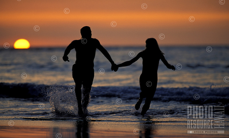 Happy couple on vacation enjoying the sunset running on the beach