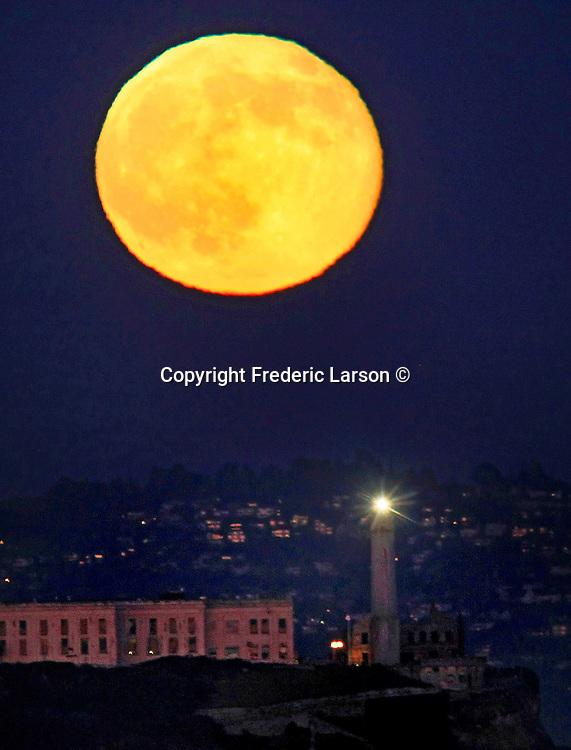 The full moon rising over Alcatraz Island in San Francisco, California.