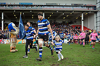 Charlie Ewels, mascots in hand, leads the Bath Rugby team onto the field. Anglo-Welsh Cup Final, between Bath Rugby and Exeter Chiefs on March 30, 2018 at Kingsholm Stadium in Gloucester, England. Photo by: Patrick Khachfe / Onside Images