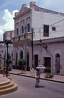 Woman with a parasol crossing a street in Old Mazatlan, Sinaloa, Mexico. Taken in 1991 before the latest restoration of Old Mazatlan.