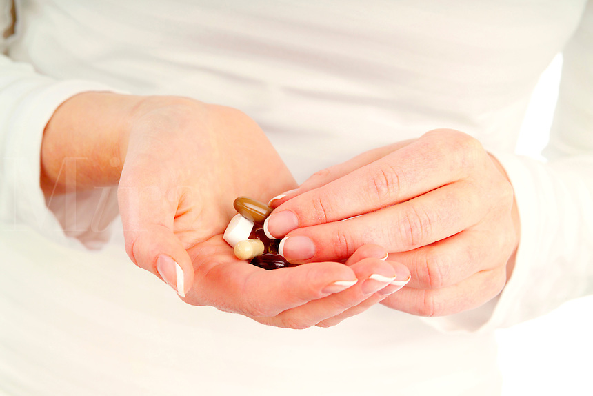 Close up of a woman with a handful of vitamins and supplements