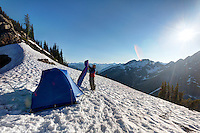 Backpacker fluffing sleeping bag at tent in snow, near Maple Pass, North Cascades, Washington, USA