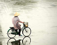 Rider on bike in rain downpour in Saigaon/Ho Chi Mihn CIty Vietnam during Rainy season.