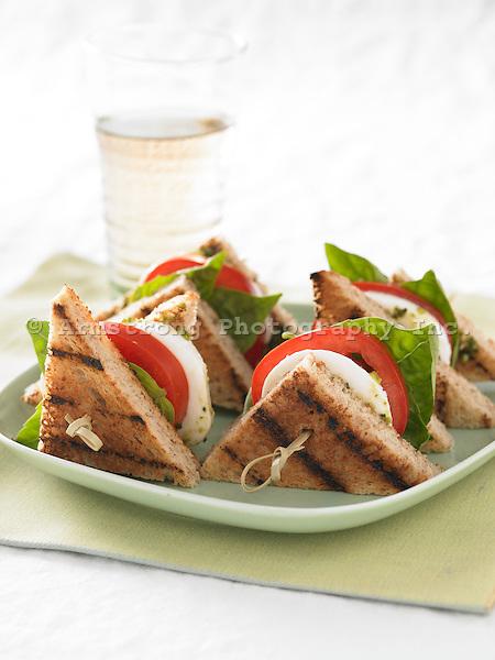 Small sandwich triangles with grilled whole wheat bread, fresh mozzarella, tomato, pesto, fresh basil, and drink.