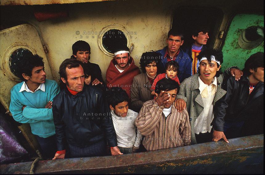 Brindisi 8 Marzo, 1991. Immigrati Albanesi nel porto di Brindisi subito dopo il loro sbarco. Migliaia di Albanesi arrivarono al porto di Brindisi utilizzando ogni tipo di imbarcazione, dopo la caduta del regime comunista in Albania. Albanian people at the Brindisi harbor. Thousands of albanian refugees reached Italy after the fall of the comunist regime. The city of Brindisi, south Italy was invaded by a mass of desperate and poor people.